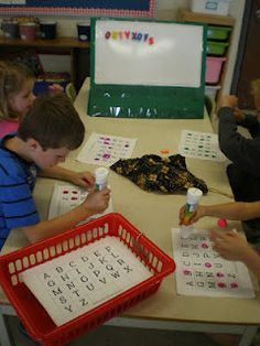 Student pulls a magnetic letter out of bag, puts it on board, everyone marks charts with bingo dot