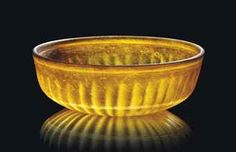 A Roman amber glass bowl, circa 1st century A.D.  The exterior with tapering ribs, the interior with two wheel-cut concentric grooves