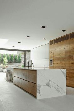 SLEEK WATERFALL KITCHEN ISLAND COUNTERS Expansive kitchen with great wood cabinetry, concrete floor, marble kitchen island and wall of windows!Expansive kitchen with great wood cabinetry, concrete floor, marble kitchen island and wall of windows!