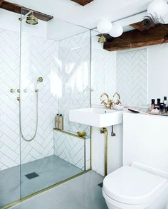 Bathroom in ciment brass and white tiles in fishbone pattern. Love the drain…