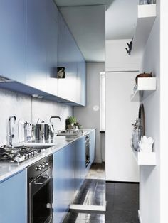Blue and white kitchen doubled with a mirror.