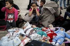 Five Syrian babies, three of them triplets (L to C), are seen lying in blankets among their relatives following the arrival of refugees and migrants on board the passenger ferries Blue Star Patmos and Eleftherios Venizelos from the islands of Lesbos. Shameful DB!
