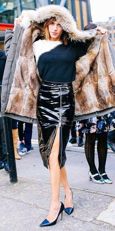 Alexa Chung in a patent leather slit skirt, fur coat and tucked in sweater