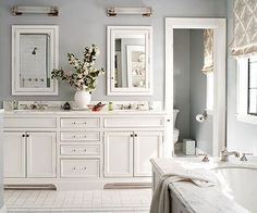 Symmetry rules in this classic white master bathroom. The double vanity features traditional inset cabinet doors and a lucite handles for extra glamour. A mixture of marble -- in counters, floor, and tub surround -- add visual interest to the all white room./