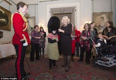 Alice Leigh tries on the bearskin of Captain Matt Wright of the Welsh Guards with the help of Camilla