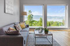 Lys og koselig stue med store vinduer og fantastisk fjordutsikt.