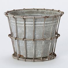 "Crate Flowerpot  $18.00  Worn metal wrapped in wire makes a rustic base for budding blooms.    - Metal  - Drainage hole not included  - Indoor use  - Imported    5""H, 6"" diameter"