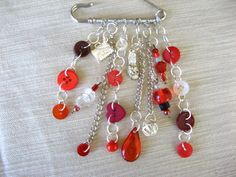 Kilt pin with red buttons and beads; and silver charms
