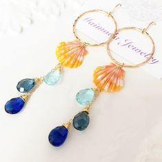 Two petite orange sunrise shells and cascading blue ombré gemstones dangle beautifully hand wrapped in 14k gold filled wire. Sunrise shells are dimel size ( about 14-15 mm) Ombré dangle are make with