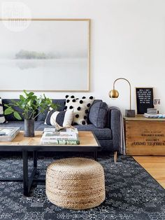 Chic interiors. Blue rug, cushions with pom poms, planters and stylish furniture.