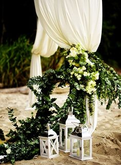 Eucalyptus, citrus branch leaves, full white blooms, draped fabric and gorgeous lanterns enhance a beachfront ceremony setting.