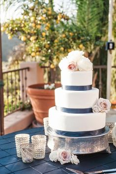 Simple wedding cake idea - three-tiered, fondant-frosted wedding cake with flowers + blue ribbon {Andrejka Photography}
