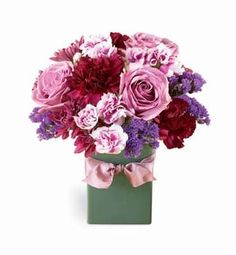What a beautiful mix! All shades of purple! Lavender roses, purple carnations and variegated mini carnations mingle freely with deep purple cushion poms and statice.  All are arranged in a square ceramic vase trimmed with a lavender ribbon. If they love purple - they'll love this bouquet!