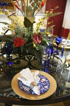 A table set for a semi-formal dinner on a wrought-iron glass-topped table. The…