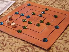 Merrills is a game that has survived the centuries and is still played today. Today is is known as Nine Men Morris. This is a handcrafted leather board game with glass playing pieces. It contains three dice for the variation found in the Alfonso X manuscript. The game board has Celtic style drawings on the board.