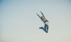 Young man jumps in air by robcampbell | Stocksy United