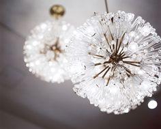 Modern Lighting - A grouping of transparent light fixtures with brass centers