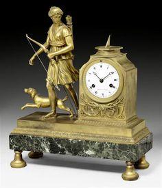 """KAMINUHR """"DIANE CHASSERESSE"""", Empire, das Zifferblatt sign. CH. OUDIN ELEVE DE BREGUET (Charles Oudin, geb. 1772), Paris um 1810. Vergoldete Bronze und """"Vert de Mer""""-Marmor. Stehende Diana in faltenreichem Gewand, mit Pfeilbogen und Hund, neben ihr postamentförmiges Gehäuse mit Sonnenuhr, auf gestuftem, rechteckigem Sockel mit gequetschten Kugelfüssen. Emailzifferblatt mit römischen Stunden- und Minutenzahlen. Pariser Werk"""