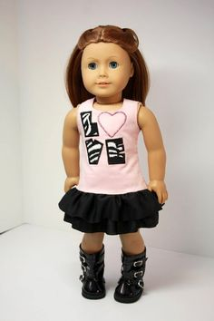 """Perfect for Valentines Day! The dress is made from pale pink corduroy with """"LOVE"""" appliqued in a zebra print. There are 2 jersey black ruffles and a velcro closure in the back. By Diane"""