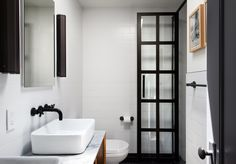 An austere palette defines the master bathroom, with subway tiles from Classic…