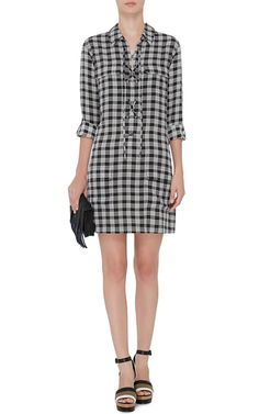 Founded in 1976 by Christian Restoin—husband of Carine Roitfeld— the French heritage brand continues to set forth gamine silk creations coveted by the fashion elite. This **Equipment** dress exudes effortless chic in black and white checked silk with a lace up front.