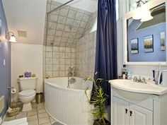 Another small bathroom in a tight upstairs. I love how they fit in a modern soaking tub. I also love how the hand-held shower head has a hanging hook on the diagonal wall.    As seen in a carriage house remodel on 2nd Ave.