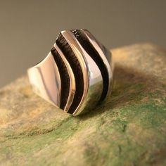 "This is a very contemporary ring featuring three very deeply carved, oxidized ""rivers"". There is a ridge that runs along the top in a gentle curve. A very classy ring that could be worn casually, or with an upscale outfit. The top width of this piece measures 17mm, or about 5/8 of an inch at its widest."