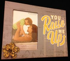 """Distressed picture frame that holds a 4"""" x 6"""" photo. Covered in paper with the words 'You Raise Me Up' printed in the style of a vintage yellow lighted sign. The frame is also accented with a yellow, brown, and black patterned tin flower. Dimensions are approximately 10"""" x 8"""" x 0.25"""". Each piece is handmade with love and truly one of a kind."""