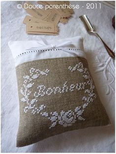 Coussin Bonheur: white cross stich on burlap