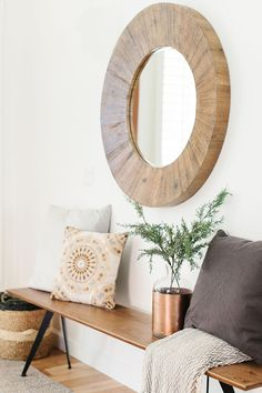 Well styled front entry space with a round wood framed mirror, pillows, narrow bench, baskets and a rattan rug.