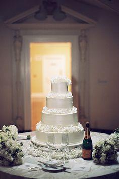 A formal, four-tier white wedding cake | @tecpetaja | Brides.com