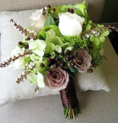 Bridesmaid bouquet in the sophisticated color palette of ivory, brown, green, and mauve-lavender.