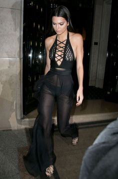 Kendall Jenner wears a sheer lace-up halter top with sheer wide-leg pants by Balmain and strappy sandals
