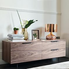 The slim profile on the Antwerp TV unit is covered in a warm walnut veneer and sat on equally slim, slightly recessed, rounded black powder coated metal legs.  The overall effect is elegance which is further emphasised with its complimentary horizontal handles, centrally placed on the two drawer tops and the cabinet door which all have soft close mechanism. The interior of the cabinet has a single, height adjustable, shelf and a centrally located cable management hole. The TV unit comes…