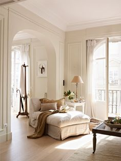 high ceilings. shades of white. arched doorways. light flooring.