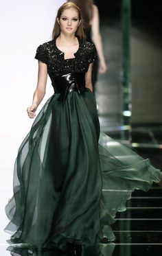 Magic in black. Love the sheer flowing skirt with the stark, black leather waist.