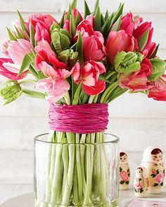 Attractive display with raffia or ribbon for helping tulips from flopping (living at home magazine). Another method: wrap branches around vase with raffia or color-coordinated ribbon; branches hold up tulips and add rustic charm.