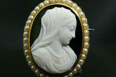 Camée néo-Renaissance, en agate onyx, à deux couches (blanc sur fond noir), relief modelé, représentant un profil de la Vierge à droite, la tête voilée, le visage baissé, les yeux mi-clos. Ce type s'inspire d'un modèle de la Renaissance italienne. Monté en broche.