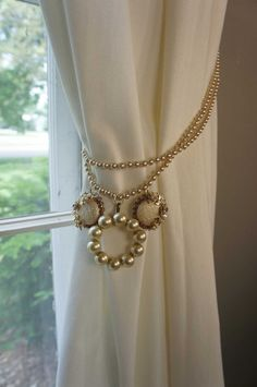Pearls, the queen of gems, and pink funky earrings are combined to make this one of a kind curtain tie back. Pearly vintage love!