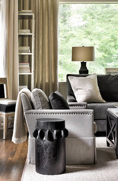 This living room has a large picture window that looks out into the trees & a cool neutral palette of grey & tan. I love the velvet upholstery with nailhead trim. A lovely and serene space....V