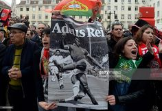 Two women hold a poster depicting Benfica football legend Eusebio da Silva Ferreira and reading 'Goodbye King' as a car with his coffin passes by, in Lisbon on January 6, 2014. Portugal paid final homage today to Portuguese footballing legend Eusebio, also known as the 'Black Panther', whose death has sparked worldwide tributes. Eusebio da Silva Ferreira died of cardio-pulmonary arrest early on January 5, aged 71.