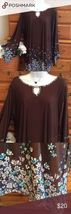 """❤️ HP ❤️ Jon & Anna Brown And Floral Tunic NWT 98% polyester and 2% spandex.  Brand new with tags.  Color is a deep brown with blue, teal green and white flowers.  Angled sleeves.  Approximately 32"""" in length and when laid flat and measured from armpit to armpit it is 25"""" across.   Gold tone emblem at the top neck line. Feels like a liquid knit.  Thank you to @belladesigns777 for the Host pick during  the Style Crush Party 11/28/17 Jon & Anna Tops Tunics"""