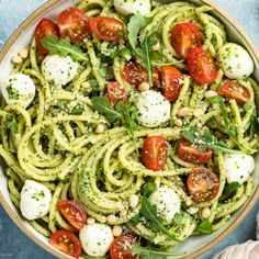 Overhead shot of Arugula Pesto Pasta tossed with mozzarella pearls and halved cherry tomatoes in a white bowl with a ramekin of grated parmesan cheese, a tan linen and vine-ripe cherry tomatoes arranged around the bowl. Basil Pesto Pasta, Salsa Pesto, Mozzarella Pasta, Pesto Pasta Salad, Mozzarella Pearls, Arugula Recipes, Pesto Pasta Recipes, Cherry Tomato Pasta, Cherry Tomatoes