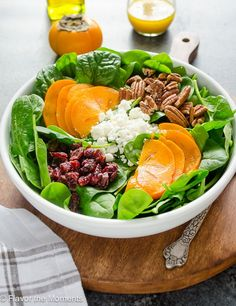 Persimmon and Spinach Salad is baby spinach tossed with sweet persimmon, chewy dried cranberries, salty feta, and crunchy pecans in an orange maple vinaigrette. It's a delicious fall salad that's perfect for holidays!