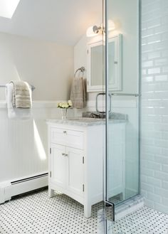 Lovely bathroom design with skylight, greige walls, chair rail with beadboard, Restoration Hardware Cartwright Powder Room Vanity Sink White with white carrara marble counter top, white mirror medicine cabinet, Pottery Barn Mercer Double Horizontal Sconce, polished nickel sconces & faucet, marble, basketweave tiles floor, subway tiles shower surround and frameless glass shower.