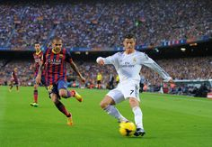 Cristiano Ronaldo of Real Madrid CF (R) crosses the ball beside Dani Alves of FC Barcelona during the La Liga match between FC Barcelona and Real Madrid CF at Camp Nou stadium on October 26, 2013 in Barcelona, Catalonia.