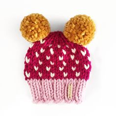 Two pom-poms are twice the fun in this handmade, chunky knit hat for babies and kids! Featuring a tiny heart design around the outside, this beanie is sure to keep them adorable and warm all season lo