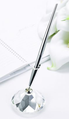 Faceted glass base with silver-tone pen. Pen writes in black ink. 2 3/4