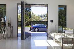 La entrada principal a la casa se hace a través de una puerta de cristal (sin cerradura: se abre mediante un código) de gran grosor, que gira sobre sí misma desde su parte central.