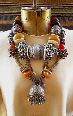 by Helen Nelson-Reed   Bottom Necklace; pendant is from Afghanistan, vintage, hand made of alpaca (silver metal alloy). Other beads include antique African trade beads made in Italy during the 2nd half of the 19th century, old Indian silver filled with wax beads (to prevent denting) vintage African coins, Moroccan zebra shells and vintage & contemporary beads from Indonesia, an antique Bohemian red hummingbird egg bead, vintage bone disks, and tribal amber - resin beads.   SOLD